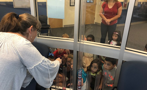 Students watching a scientific experiment through a window