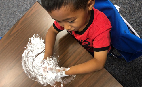 Boy playing with shaving cream on his desk