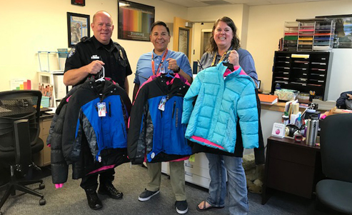 Police Officer and school staff holding donated winter coats