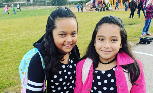 Two girls dressed alike in polka dot dresses