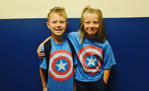 A boy and girl wearing matching Captain America T-shirts