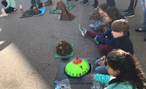 Students showing their handmade volcano projects