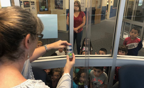 Students watch a science experiment through a window