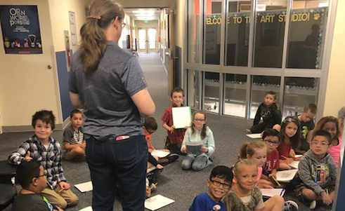 Students sit on the floor listening to a teacher