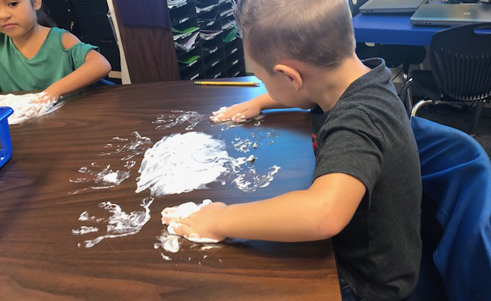 Boy swirling shaving cream around on his desk