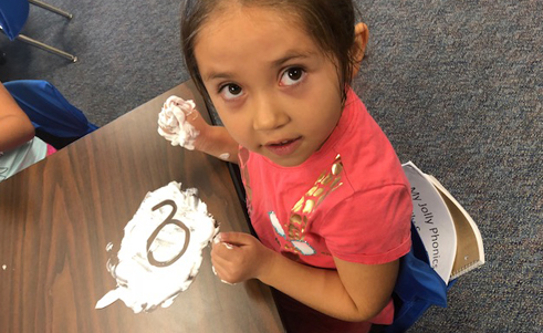 Girl making designs in shaving cream on her desk