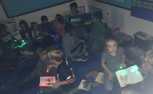 Class of students doing an activity with colored lights