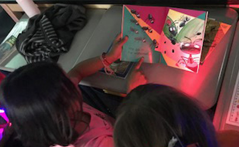 Students reading a book together by colored light