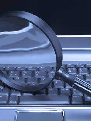 Magnifying glass on top of a keyboard