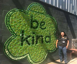 Teacher poses in front of the Be Kind mural