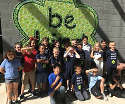 Students pose in front of the Be Kind mural