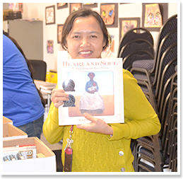 Smiling woman holding up a book titled Heart and Soul