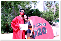 Graduate wearing a graduation robe posing with an adult in front of a Red Raiders 2020 sign