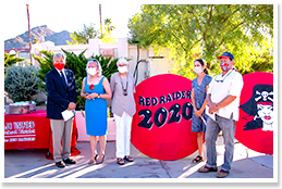 Adults posing in front of a Red Raiders 2020 sign