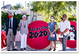 Adults wearing masks posing in front of a Red Raiders 2020 sign