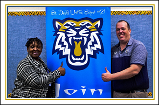 Superintendent and an administrator give a thumbs up in front of a St. David Unified School District #21 poster