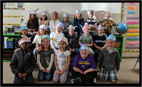 Class of students wearing paper hats