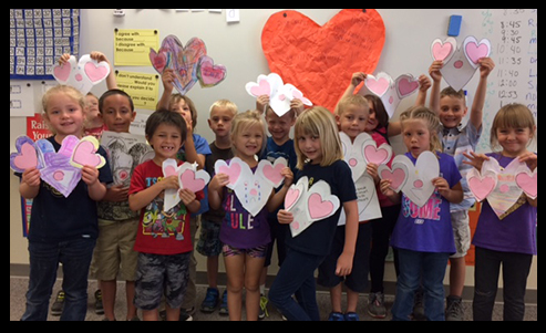 Group of students stand in front of heart shaped decoration