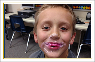 Male student smiles with popped bubblegum on his lips