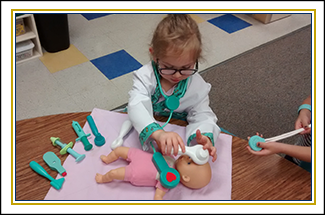 Female student playing as a doctor with a toy baby