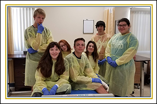 Group of students dressed in hospital attire pose together