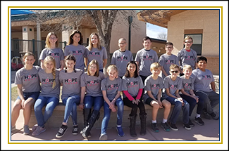 Group of students wearing Hope Squad t-shirts posing together outside