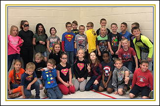 Elementary school students wearing superhero shirts pose together