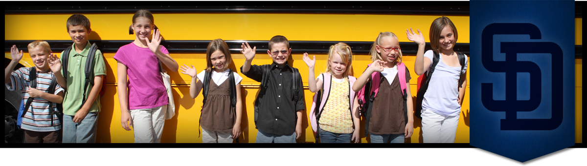 students in front of a bus waving