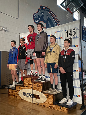Wrestling team members stand on award stage