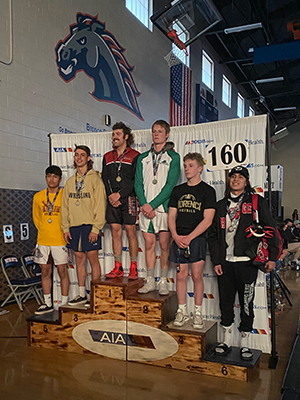 Wrestling team members stand on award stage with medals