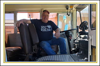bus driver sitting in his bus wearing a shirt that says You Matter