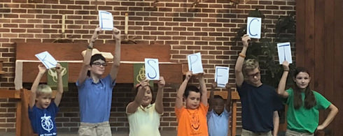Students holding signs spelling out RESPECT