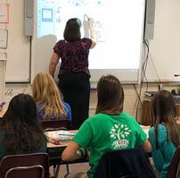 Teacher using smart board in front of class