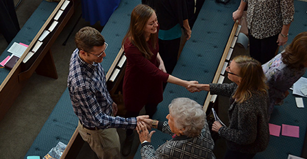 young couple shakes hands with people in church