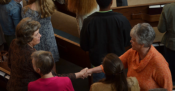 2 women shake hands in church