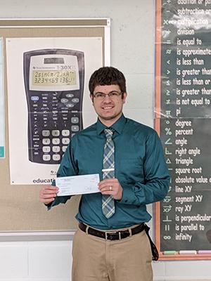 Christian Sevinsky holding his grant check