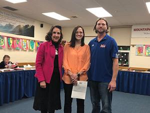 Jamie White stands with Superintendent Karen K. Voigt and Jason Richmond, School Board President