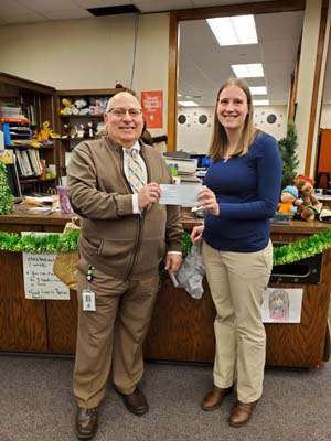 Dr. Toth presents check to Ms. Ellen Stolarski, Middle School Librarian.