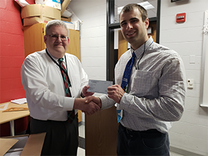 Mr. John Chelednik receives his check from the superintendent.