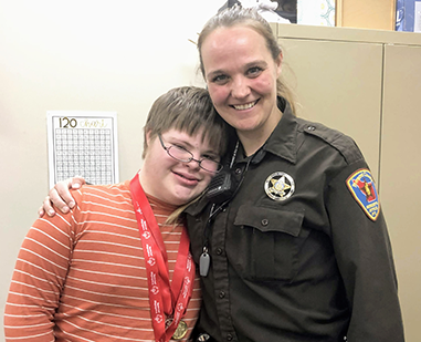 Woman from the Fremont County Sheriff office posing for a picture with a student wearing award ribbons