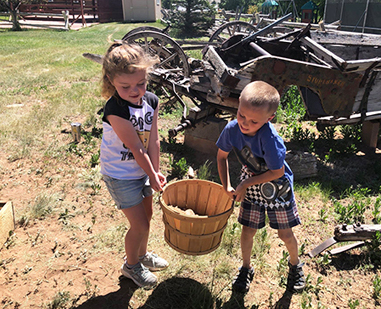 Elementary students, Bristol and Payton, carrying a bucket outside