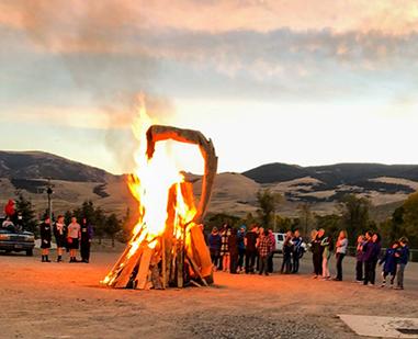 An object burns as onlookers watch