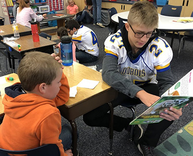 student in a football uniform reading to a young student