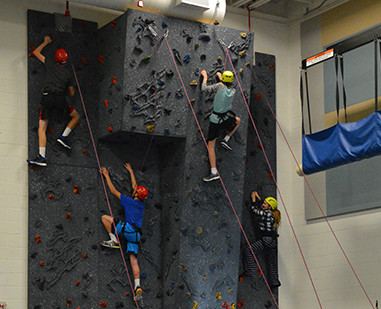 Students on a rock climbing wall.