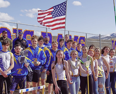 Students on bleachers next to United States flag