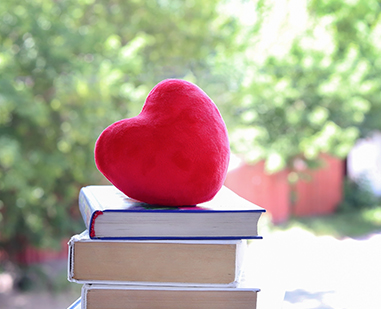 stack of books with a heart on top