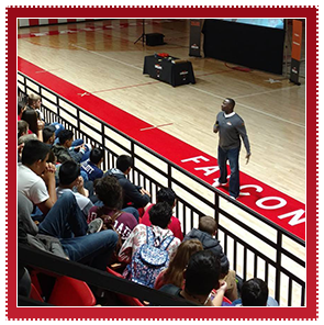 Staff member speaks to students during an assembly in a gym