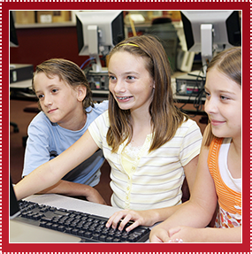 smiling children using a computer