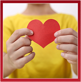 Elementary school boy in yellow shirt holding a red paper heart