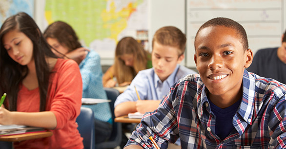 Smiling student sits in a classroom